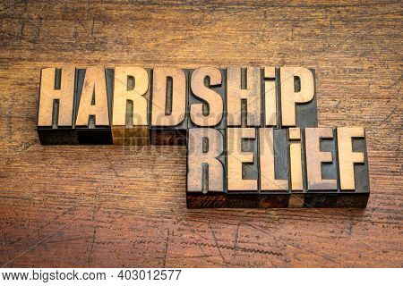 hardship relief word abstract in vintage letterpress wood type against rustic wooden background, help, support and assistance