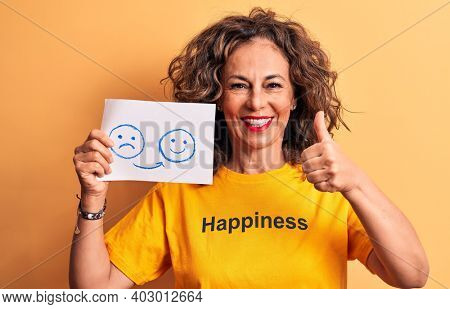 Middle age woman wearing t-shirt with happiness word holding sad to happy emotions paper smiling happy and positive, thumb up doing excellent and approval sign