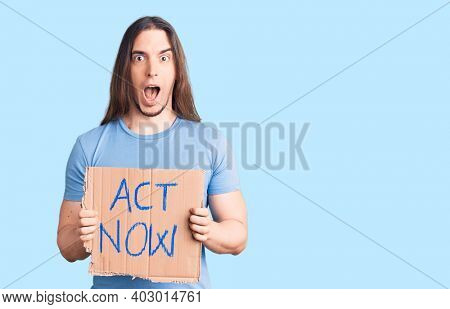Young adult man with long hair holding act now banner scared and amazed with open mouth for surprise, disbelief face