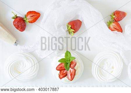 Portion Australian Dessert Pavlova With Airy Butter Cream, Fresh Strawberries And Mint On A White Pl