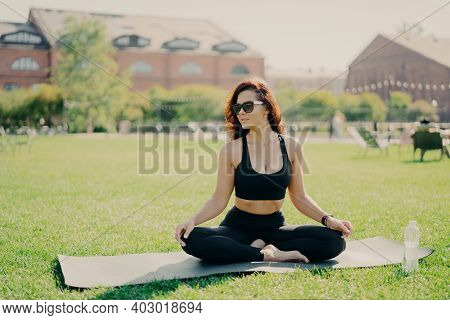 Relaxed Brunette Woman Sits On Fitness Mat On Lotus Yoga Pose Wears Sunglasses Cropped Top And Leggi