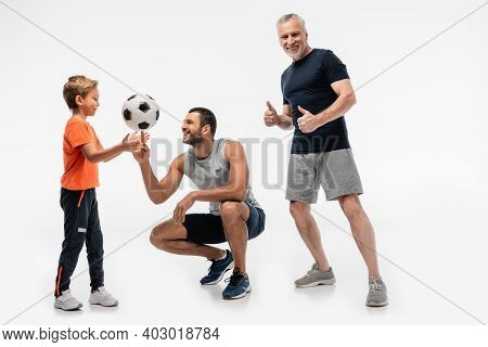 Cheerful Granddad Showing Thumbs Up Near Father And Son Playing With Soccer Ball On White