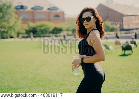 Summer Activity And Energy Concept. Brunette Sporty Woman In Sports Clothes Holds Bottle Of Water We