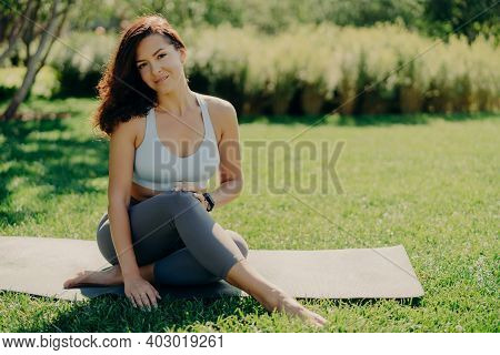 Photo Of Brunette Sportswoman Has Rest After Fitness Training Sits On Karemat With Bare Feet In Acti