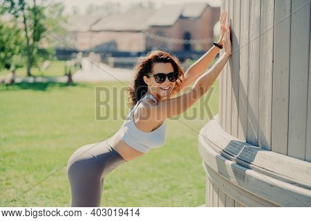 Slim Woman With Perfect Body Shapes Leans With Hands At Something Smiles Positively Dressed In Top A