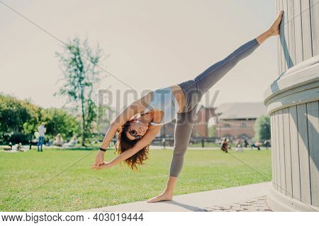 Flexible Slim Woman Does Stretching Exercises Outdoor Stays In Good Physical Shape Dressed In Croppe