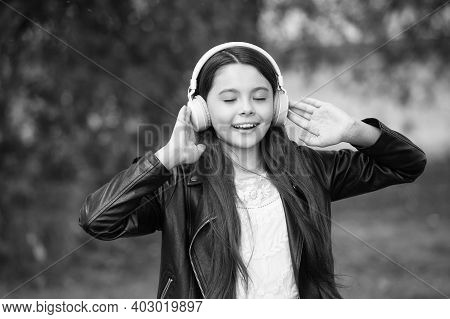 Shes Ear For Music. Happy Child Wear Ear Phones Outdoors. Small Girl Listen To Music In Headphones.