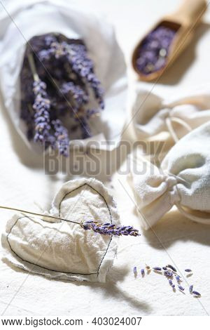 Close-up On Dry Lavender Flowers In White Tracing Paper. Hand Made Lavender Sachets On Cotton Tablec