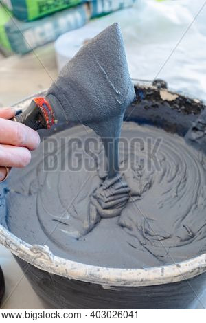 Abstract Texture Cement Mortar For The Background. A Male Hand Holds A Spatula With The Mixture Over