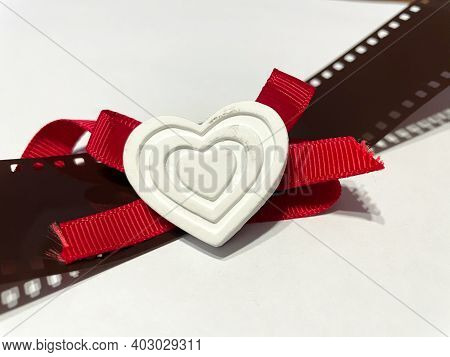 A White Heart With Red Ribbon Resting On A Photographic Film, Romantic Image For Valentine's Day