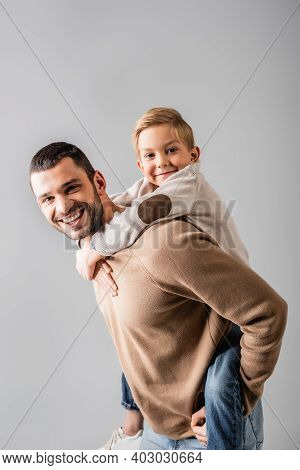 Happy Man Piggybacking Smiling Son While Looking At Camera Together Isolated On Grey