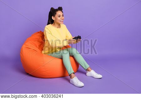 Full Size Photo Of Optimistic Girl Sit On Pouf Playstation Wear Yellow Shirt Trousers Sneakers Isola
