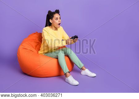 Full Size Photo Of Impressed Girl Sit On Pouf Playstation Wear Yellow Shirt Trousers Sneakers Isolat