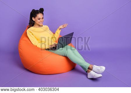 Full Size Photo Of Optimistic Girl Lying On Pouf Work Laptop Wear Yellow Shirt Trousers Sneakers Iso