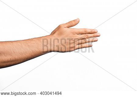 Hand of caucasian young man showing fingers over isolated white background stretching and reaching with open hand for handshake, showing back of the hand