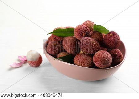 Fresh Ripe Lychees In Bowl On White Wooden Table