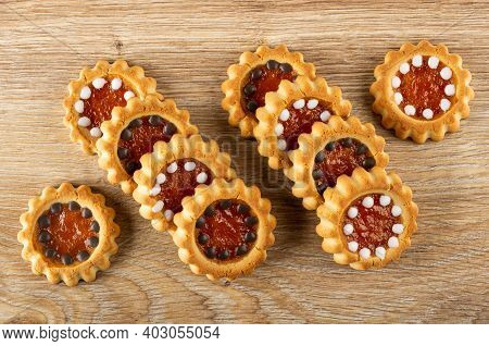 Cookies With Filling From Orange Jam And Chocolate On Brown Wooden Table. Top View