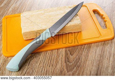 Kitchen Knife On Piece Of Peanut Halva On Orange Plastic Cutting Board On Wooden Table