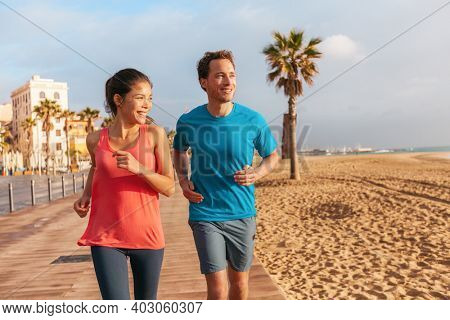 Running couple jogging on Barcelona Beach, Barceloneta. Healthy lifestyle people runners training outside on boardwalk. Multiracial couple, Asian woman, Caucasian fitness man working out, Spain.