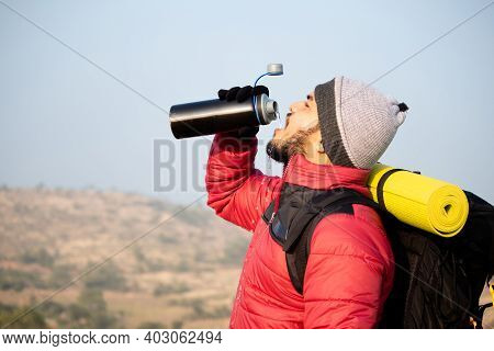 Thirsty Travler Drinking Water By Taking Break While Climbing - Concept Of Drink Water Before Feelin