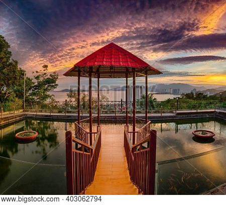 Pavilion on the pond at sunset. nha Trang city on background. Vietnam