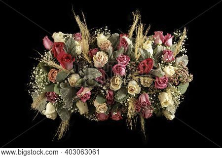 Arrangement Flower Table Centerpiece With Pink Tones Roses And Foliage. Isolated On Black Background