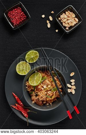 Pad Thai. Stir-fried rice noodles with chicken meat,  scrambled egg, peanuts, vegetables and sauce in bowl on gray slate background. Top view. Thai food. Setting table