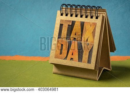 tax day word abstract - text in vintage letterpress wood type in a spiral  desktop calendar - business  financial concept or reminder