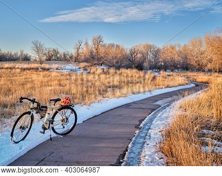 touring bicycle in late fall or winter scenery - one of numeous bike trail in Fort Collins, northern Colorado, recreation and commuting concept