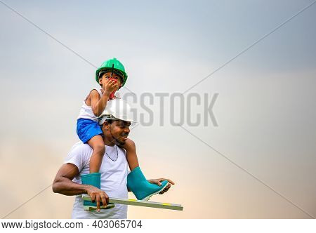 Cheerful African American Father And Son In Hard Hat, Happy Dad Carrying Son On Shoulders
