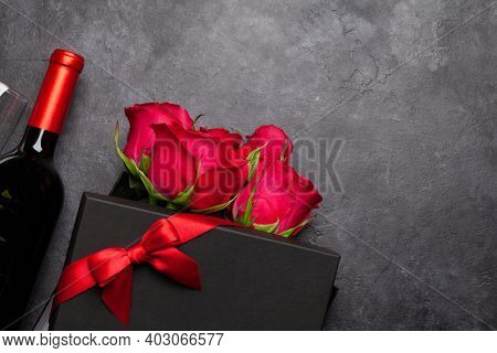 Valentines day greeting card with red rose flowers bouquet, wine and gift box on stone table. Top view flat lay with space for your greetings