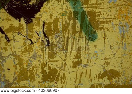 Dark Grunge Damaged Wall Background Texture With Scraped Flaking Paint And Remnants Of Graffiti In A