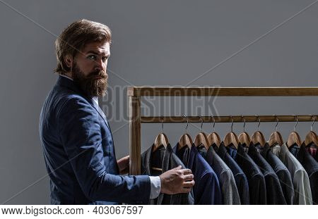 Tailor, Tailoring. Mens Suit, Tailor In His Workshop. Elegant Mans Suits Hanging In A Row. Luxury Me