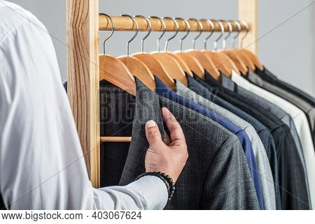 Stylish Mens Suit. Male Suits Hanging In A Row. Men Clothing, Boutiques. Man Suit, Tailor In His Wor