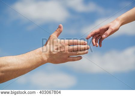 Giving A Helping Hand. Hands Of Man And Woman On Blue Sky Background. Lending A Helping Hand. Hands
