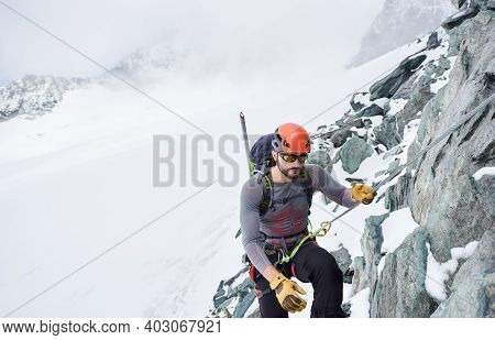 Man Alpinist In Sunglasses And Safety Helmet Holding Fixed Rope While Climbing Snowy Mountain. Mount