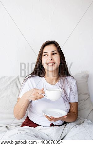 Young Brunette Woman Sitting Awake In The Bed With Red Heart Shaped Balloons And Decorations Drinkin
