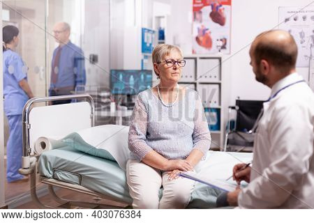 Elderly Woman Talking With Doctor In Hospital Cabinet In The Course Of Treatment. Elderly Patient Ha