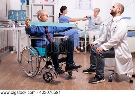 Old Man Following Therapy With Help From Medical Staff In Modern Hospital. Elderly Invalid Patients