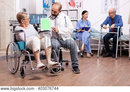 Handicapped Senior Woman Sitting In Wheelchair Discussing With Doctor Holding Tablet Pc With Green S