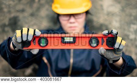 Asian Maintenance Worker Man Holding Red Aluminium Spirit Level Tool Or Bubble Levels At Constructio