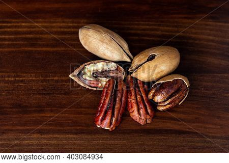 Pecan Nuts On A Wooden Table. Heap Or Stack Of Pecan. Cracked And Opened Pecan Nuts And Nuts In Shel