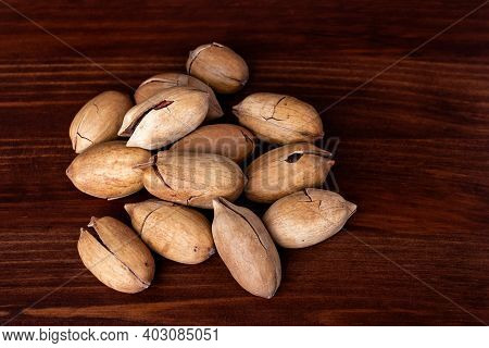 Heap Of Pecans With Clipping Path On A Wooden Background. Unpeeled Pecans Nut. Pecan Nuts Kernels