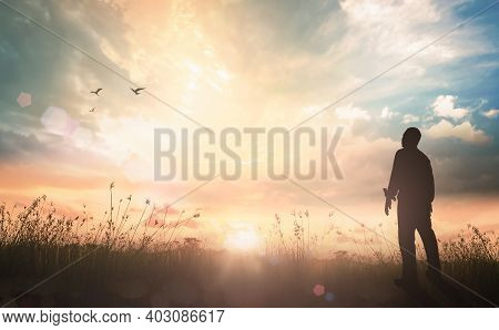 Worship And Praise Concept: Silhouette Humble Man Standing On Sunlight With Meadow Autumn Sunset Bac