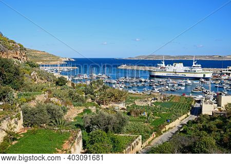 Mgarr, Malta - April 3, 2017 - Fishing Boats And Yachts Moored In The Harbour With The Gozo Ferry Mo