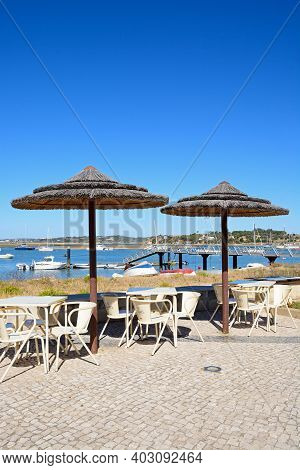 Alvor, Portugal - June 7, 2017 - Tables And Parasols On The Waterfront With Views Across The Estuary