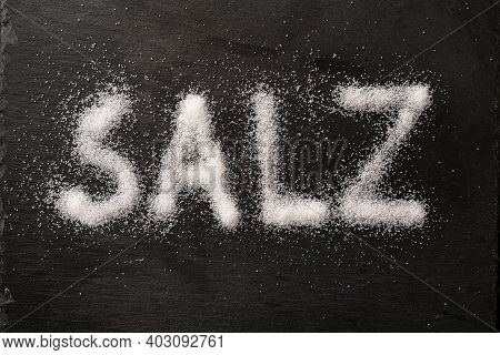 German Word Salz (meaning Salt) Written With Salt Crystals On A Dark Slate, High Angle View From Abo