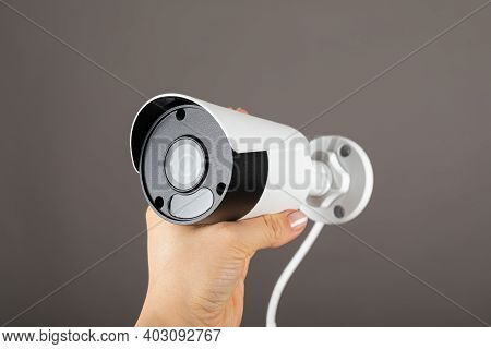 Close Up Picture Of Safety Camera In Human Hand Against Grey Background