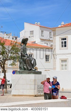 Lagos, Portugal - June 9, 2017 - A Couple Looking At A Map In Front Of The Statue Of Infante Dom Hen