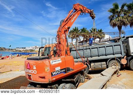 Albufeira, Portugal - June 10 2017 - Construction Worker On The Beach Moving Girders With An Excavat
